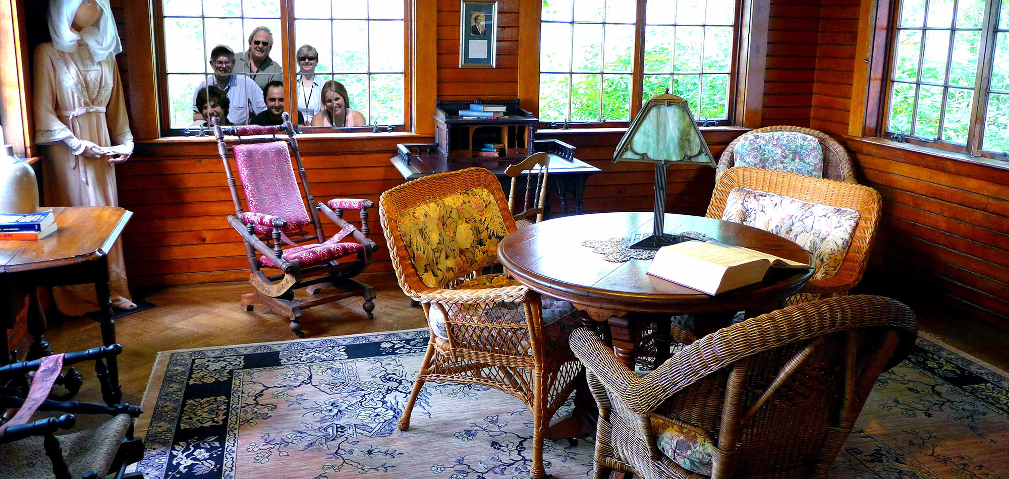 Some of the 2008 O'Neill Center Theater Critics peer into the sun room at Monte Cristo Cottage, set up to reflect the stage directions for Eugene O'Neill's final play Long Day's Journey into Night. (David Lyon for The Boston Globe)