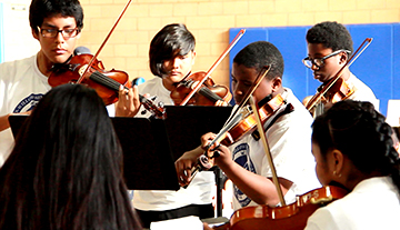 Students perform with string instruments in the Watts Willoughby Center program