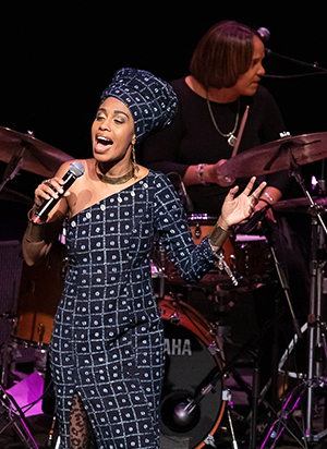 Jazzmeia Horn performs, at Royce Hall on November 9, 2018, as part of Terri Lyne Carrington's tribute to music Joni Mitchell, Tina Turner and Nancy Wilson. (Carrington in background) (c) Reed Hutchinson 2018