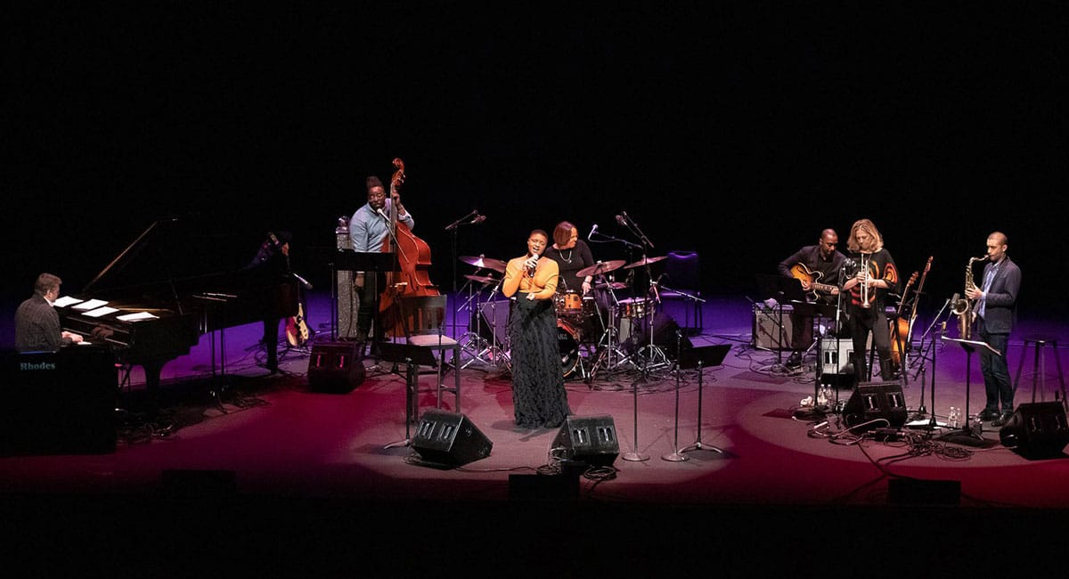 "Lizz Wright (center) performs ""Edith and the King Pin"" in Terri Lyne Carrington's tribute to the music Joni Mitchell, Tina Turner and Nancy Wilson at UCLA on November 9, 2018. Left to right: pianist Jon Cowherd, bassist Solomon Dorsey, Wright, Carrington, guitarist Marvin Sewell, trumpeter Ingrid Jensen and saxophonist Edmar Colon. Photo: ©Reed Hutchinson 2018"